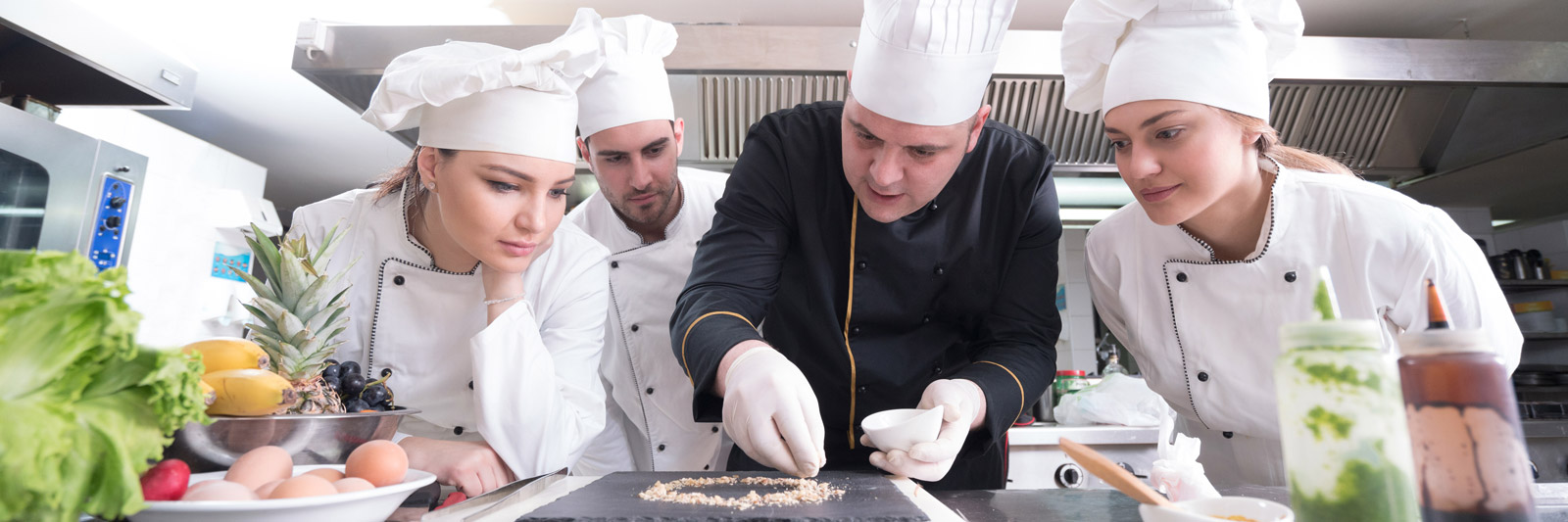 a group of commis chef apprentices watching a chef prepare a dish