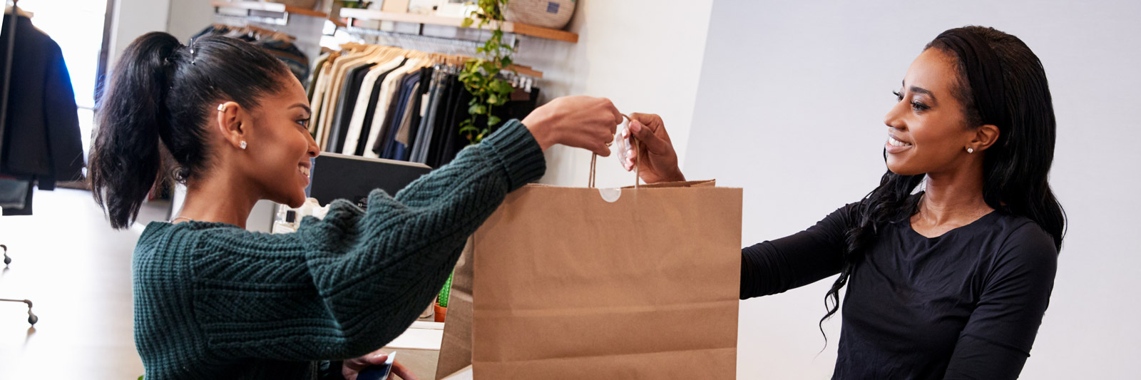 a retail assitant passing a bag across the counter to a customer