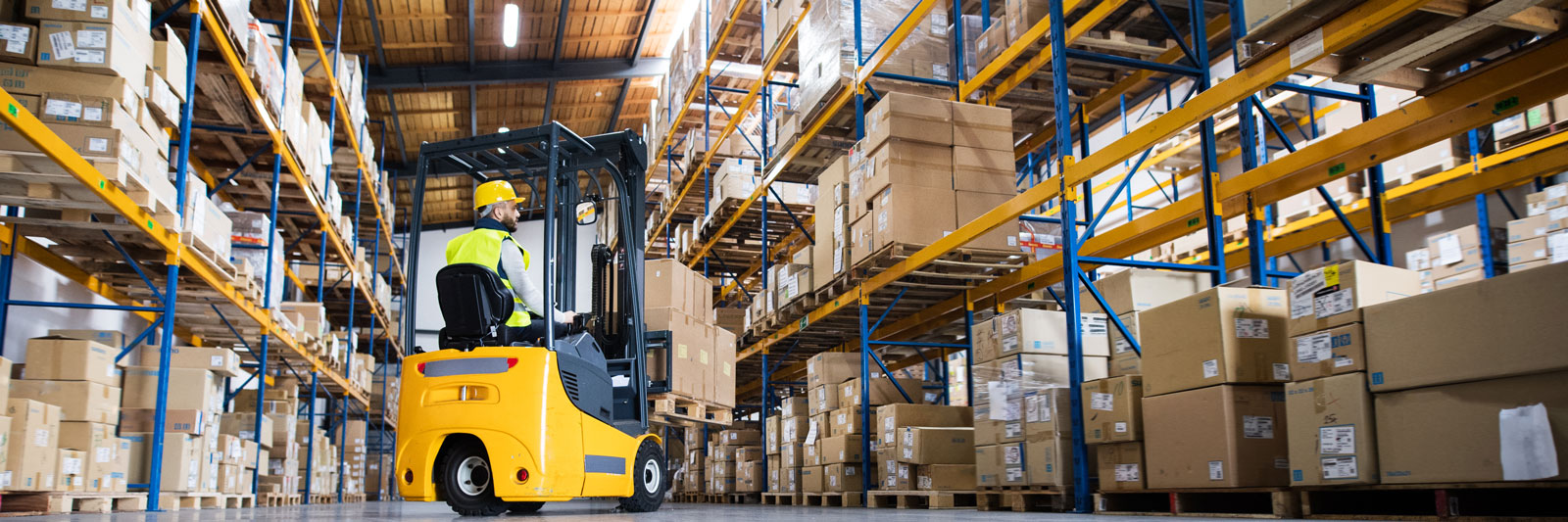 a forklift and operative in a warehouse aisle